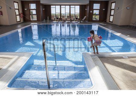 Little child enjoying swimming pool indoors. Cute toddler girl wearing armbands having fun in the water