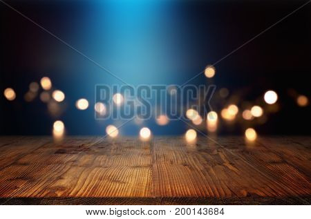 Bokeh background with blue light beam and an empty rustic wooden table for a festive christmas decoration