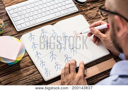 Businessman Drawing Figures To Illustrate Leadership Concept In Notebook Over The Wooden Desk