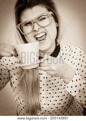 Happy woman at office drinking hot coffee or tea enjoying her break time during work. Job relax.