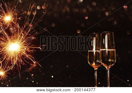 Festive background with sparkling miracle candle and champagne for new years eve