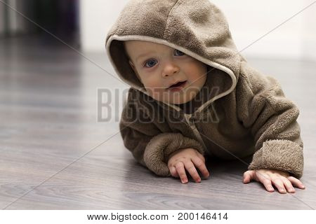 Cute 9 month child in brown fur hoody makes along arm for something.