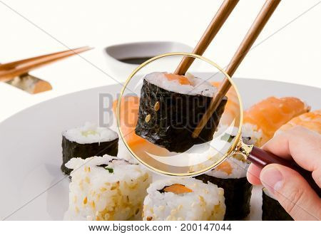Closeup of hand scrutinizing sushi served in plate through magnifying glass in restaurant