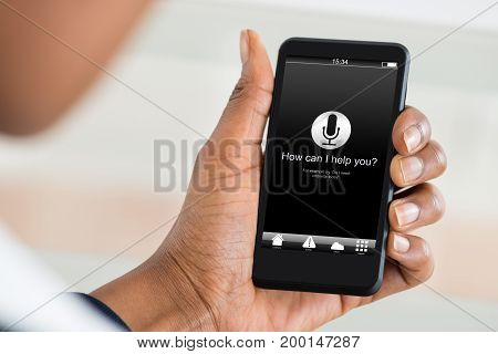 Cropped image of man holding mobile phone with how can I help you? text