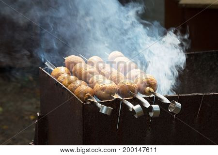 Grilled Potatoes Cooking On Metal Skewer. The Potatoes Cooked On The Barbecue On The Coals. Grill On