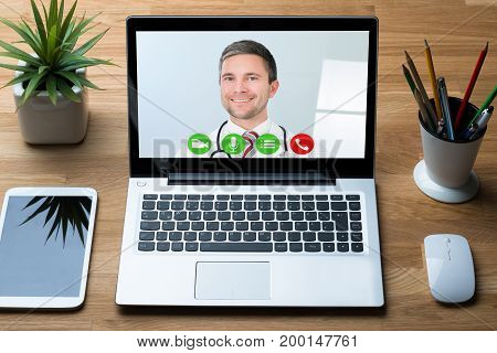 High angle view of doctor smiling while video conferencing on laptop in hospital