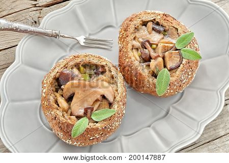 Overhead shot of plate with bread buns filled with mixed sauteed mushrooms and sage.