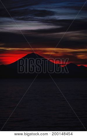 Bright tropical sunset and silhouettes of Agung volcano on the island of Bali in Indonesia. Magic colors during sunset, bright clouds and red sun light. Journey to a tropical island in the ocean.