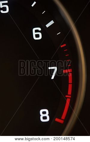Close-up of car tachometer indicator. Red rpm zone