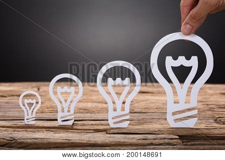 Paper light bulbs arranged in increasing order on wooden table against black background