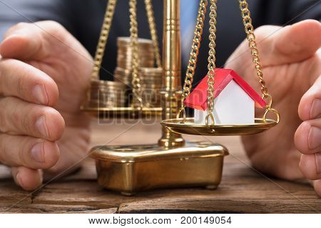 Businessman covering model home and coins on golden weighing scale at wooden table