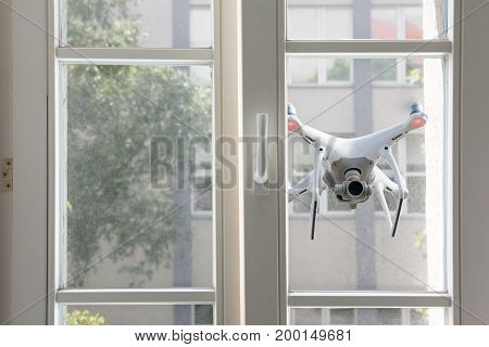Flying white quadrocopter spying through window of a house