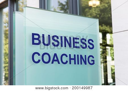 Closeup of business coaching sign on glass board outside building in city