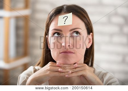 Close-up Of A Businesswoman's Forehead With Question Mark On Sticky Note