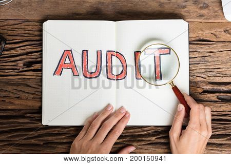 High Angle View Of A Businessperson Analyzing Audit Text With Magnifying Glass
