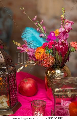 A table set vase with flowers decorate in purple and pink and orange