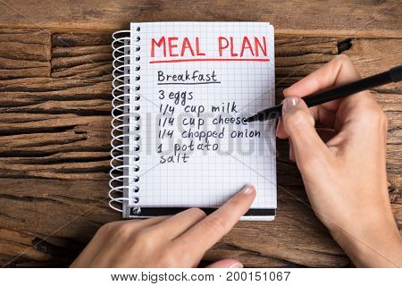 Close-up Of A Human Hand Making Meal Plan On Notebook Over Wooden Desk