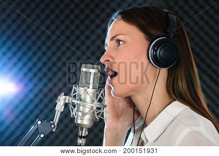 Portrait Of A Young Woman Singer With Headphones In Front Of The Microphone