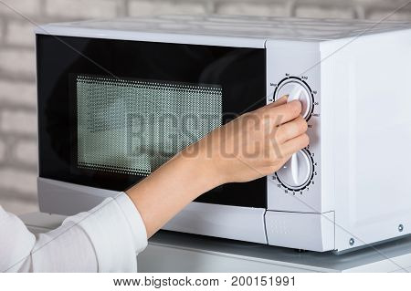 Woman Using Microwave Oven For Heating Food At Home