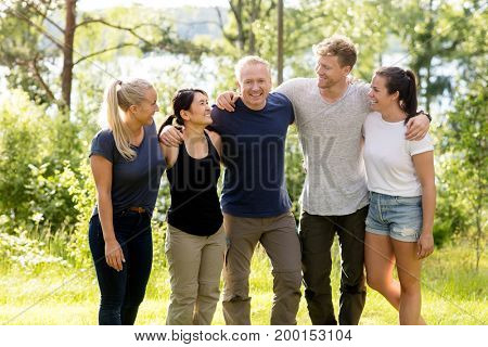 Man Standing With Arms Around Friends In Forest