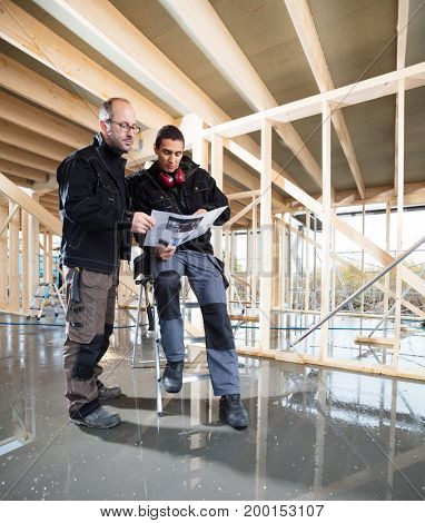 Full Length Of Carpenters With Plan At Construction Site