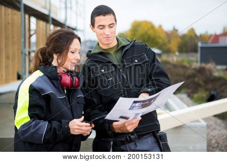 Male And Female Carpenters Discussing About Plan