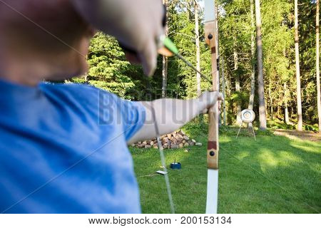 Male Athlete Aiming Arrow At Target Board In Forest