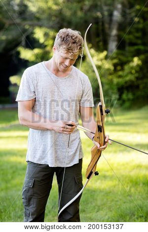 Confident Male Archer Holding Bow And Arrow In Forest