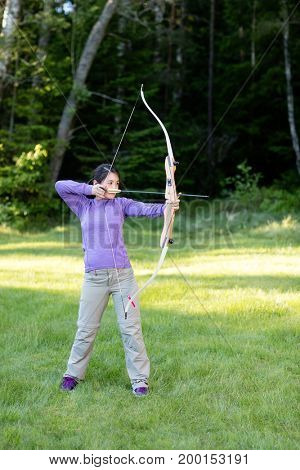Confident Woman Aiming With Bow And Arrow In Forest