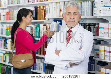 Senior Chemist Standing Arms Crossed While Customer Choosing Pro