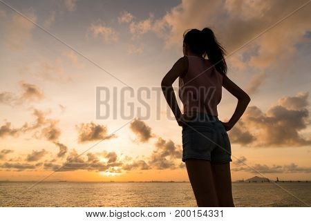 Silhouette of woman holding hand on waist