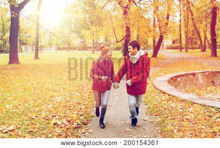 love, relationships, season and people concept - happy young couple running in autumn park and talking