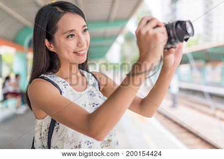Woman taking picture with camera in light rail station