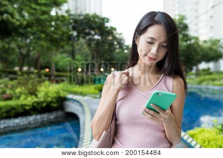 Woman looking at mobile phone in the park