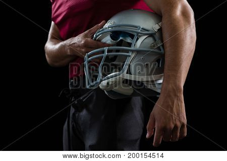 Close-up of American football player holding a head gear under his arms