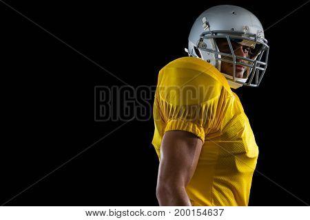 Portrait of American football player standing against a black background