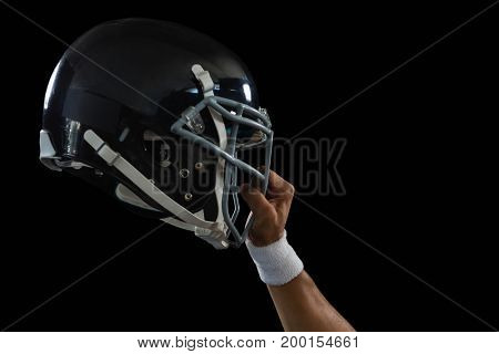 Close-up of American football player holding a head gear raised