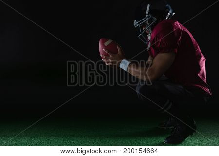 American football player sitting on toes holding a ball with both his hands on artificial turf