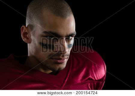 Close-up of determined American football player against a black background