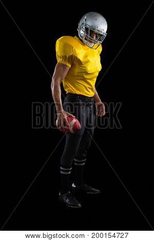 American football player holding a ball in one hand against a black background