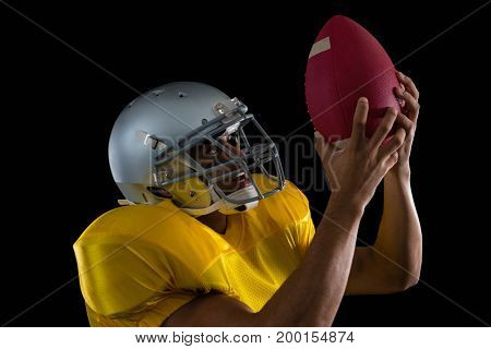 American football player looking at ball holding it in his hands against black background