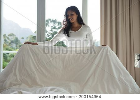 Young woman making bed by window at home