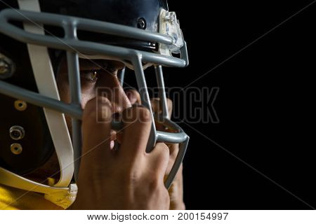 Mid section of American football player holding a head gear on his head