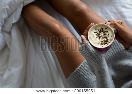 Mid section of woman having coffee on bed at home