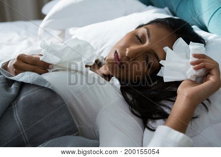 Sick young woman with tissues sleeping on bed at home