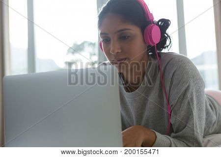 Young woman listening to music while using laptop on bed at home