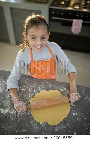 Portrait of little girl flattening dough on the kitchen counter