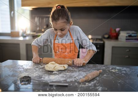 Close-up of little girl flattening dough on the kitchen counter