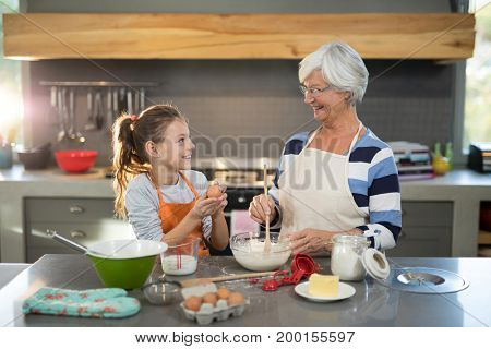 Granddaughter mixing flour in a bowl with her granddaughter in the kitchen