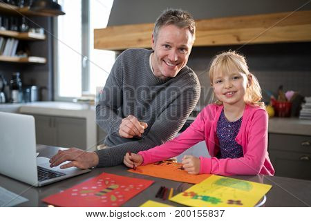 Father and daughter posing while coloring on a paper in the kitchen